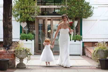 a bride walks with her flowergirl