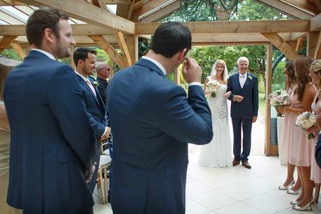 the groom sheds a tear as his bride arrives