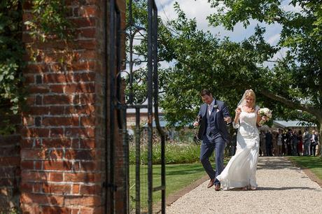 bride and groom walk through gaynes park