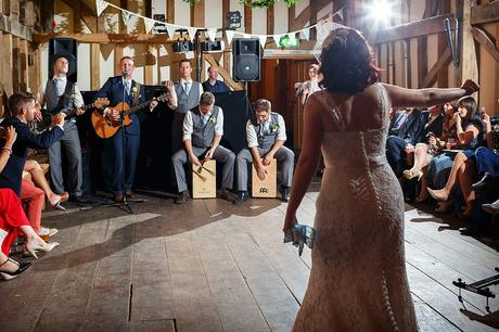 the groom and his band sing to the bride