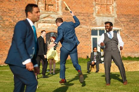 guests play rounders outside the wedding barn