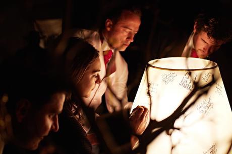 guests sign a lampshade at a barn wedding