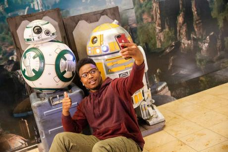 A guest at Orlando International Airport stops to take a selfie with droids from Star Wars: Galaxy's Edge outside the airport's Magic of Disney store in the Main Terminal, Nov. 16, 2019, in Orlando, Fla. The droids were brought to the airport to help travelers feel some of the fun and excitement of the new land at Disney's Hollywood Studios at Walt Disney World Resort.