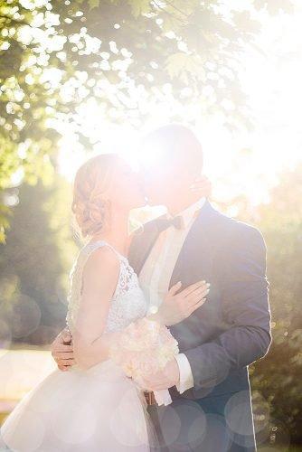 unique wedding ceremony script newlyweds kissing against the sun