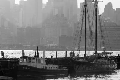 A small motor launch and a small schooner tied up at a dock in Hoboken in the early morning