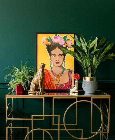 Moody, green living room decor with colourful and bold Frida Kahlo style self portrait