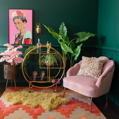 Moody, green living room decor with colourful and bold Frida Kahlo style self portrait and gold luxe round drinks trolley