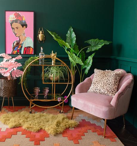 Cool living room decor with green walls, gold drinks trolley and pink velvet armchair.