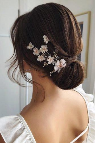wedding hair trends brown elegant chignon with white flower accessorie caraclyne.bridal