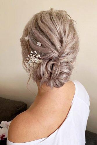 wedding hair trends blonde textured low updo with flower pins bridal_hairstylist