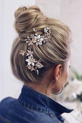 wedding hair trends classy textured high bun on blonde hair with white flower accessories tonyastylist