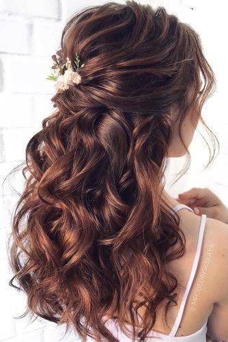 wedding hair trends curly half up half down on brown hair with gentle pink flowers mpobedinskaya