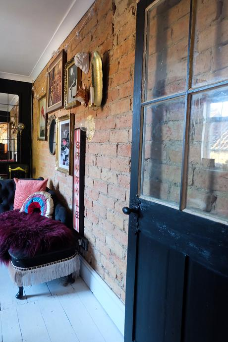 Eclectic living room with exposed brick feature wall.