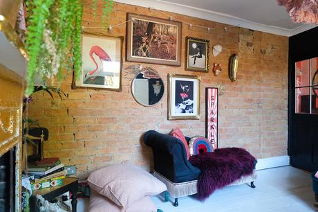 Eclectic interior decor with exposed brick feature wall.
