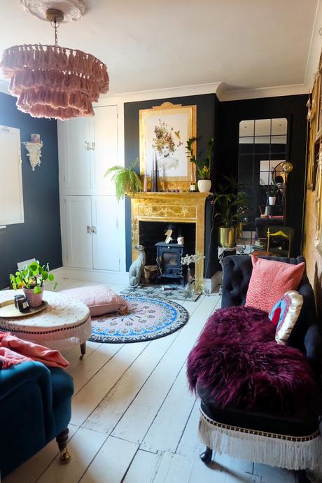 Before and after - eclectic living room decor with black walls and gold fireplace.