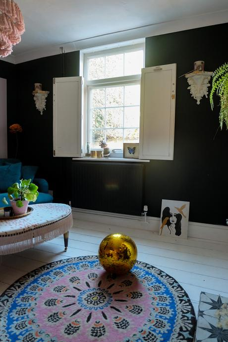Black and moody decor with white painted floorboards and colourful accents