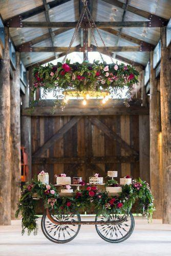 wedding dessert table ideas in a wooden barn on a cart decorated with greens and red roses toast wedding magazine via instagram