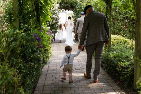 Groom holds son's hand as bride holds daughter's hand at York wedding.