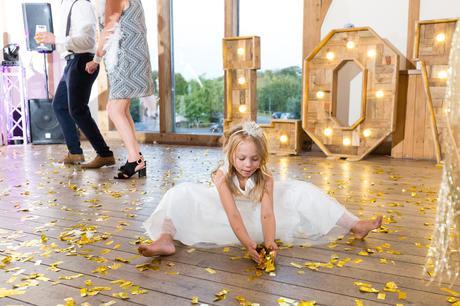 Flower girl picks up confetti off of floor at Sandburn Hall Wedding