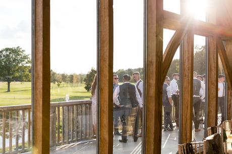 Sun shining through window at Sandburn Hall with wedding guests outside.