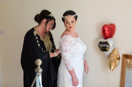 Bride's mother helps her into her dress in a Peaky Blinders themed wedding at Sandurn Hall.