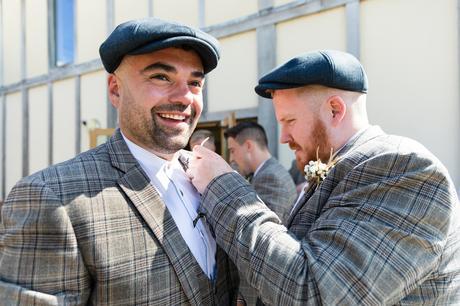 Groomsman helps groom put on buttonhole at Sandburn Hall wedding.