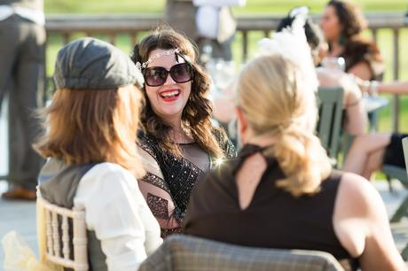 Guest dressed in 1920's style dress smiling and laughing in the sunlight.
