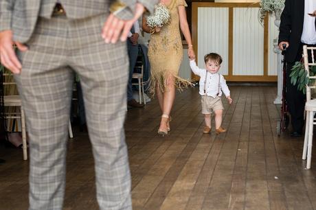 Adorable pageboy in braces walks up aisle at Sandburn Hall wedding.