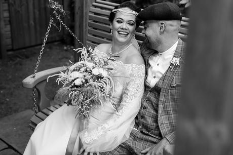 Bride & Groom laughing and sitting on swing at Sandburn Hall Wedding.