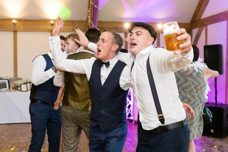 Guests dancing with arms around each others shoulders at York wedding.