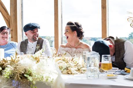 Bride & groom laughing during fun wedding speeches.