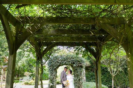 Bride & Groom standing under arbour at Sandburn Hall wedding.