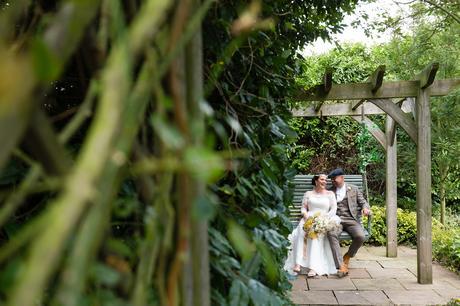 Wedding couple sitting on bench swing at Sanburn Hall wedding.