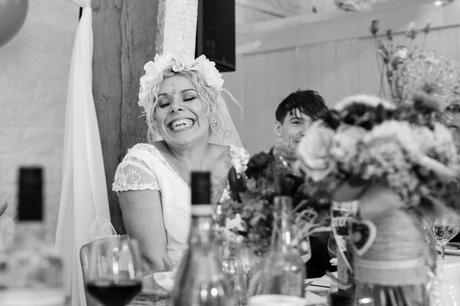 Bride smiles sweetly during speeches at East Riddlesden Hall.