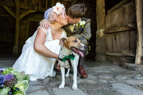 Bride and groom kiss behind their adorable dog at Yorkshire wedding.