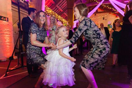 Flower girl dancing with other guests at East Riddlesden Hall wedding with purple lighting.