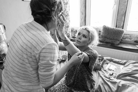 Bride helps sister put on her makeup.