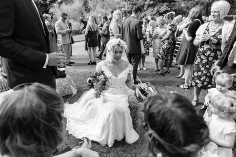 Bride sits on hay bales at barn wedding whilst visiting with guests at East Riddlesden Hall.