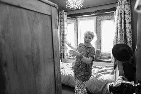 Bride makes funny face as she gets ready before her East Riddlesden Hall wedding.