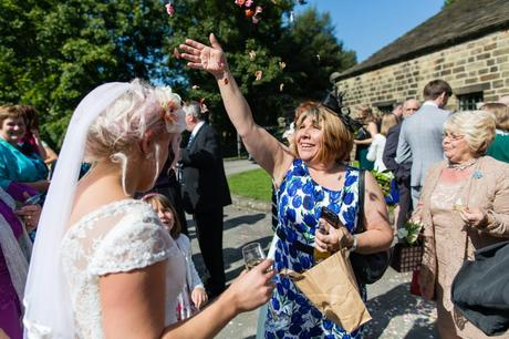 Guest throws confetti at bride outside of barn at East Riddlesden Hall