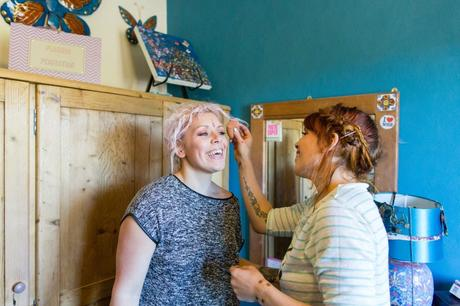 Bride's twin sister helps her do her makeup in a room with blue walls.