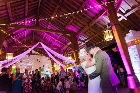 Bride and groom have first dance in barn with purple lighting.
