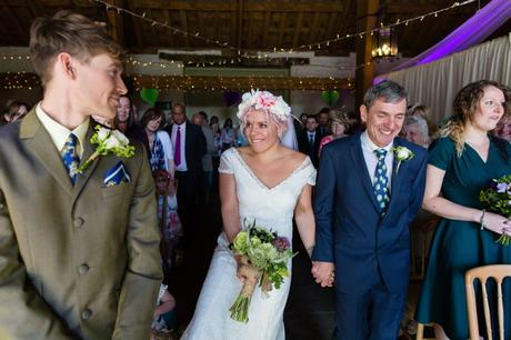 Bride smiles and kicks groom as she reaches the top of the aisle at East Riddlesden Hall wedding.