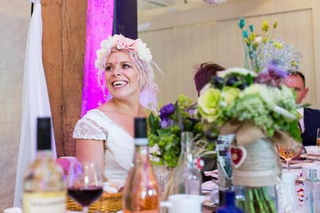 Bride with pink hair smiling during speeches at Yorkshire wedding.