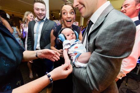 Adorable baby wearing ear defenders at London wedding.