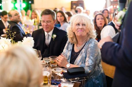 Groom's mom smiles during wedding speeches.