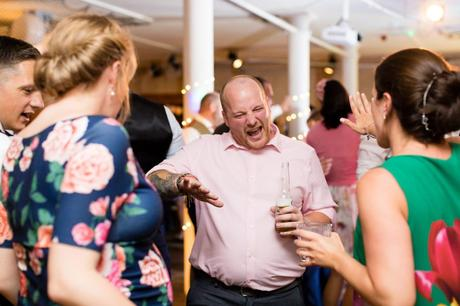 Wedding guest dancing whilst holding a beer.