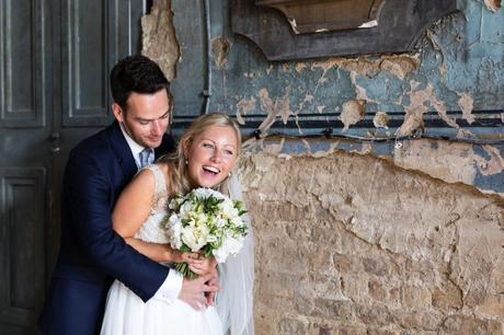 Bride and groom laugh next to de-constructed wall at the Asylum in London