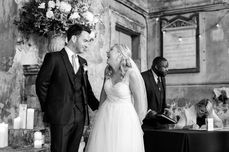 Bride and groom look at each other and smile/laugh at London Asylum wedding.