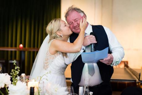 Bride kisses dad on the cheek during speeches at London wedding.